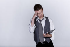 Man worried looking at clipboard, studio shot Stock Images