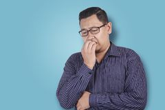 Man Worried or Nervous Expression, Biting Nails. Portrait of young Asian man looked worried or nervous of something bad, look down and biting his nails stock photo