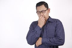 Man Worried or Nervous Expression, Biting Nails. Portrait of young Asian man looked worried or nervous of something bad, look down and biting his nails royalty free stock photo