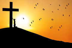 Man worship the cross. Christian background: Silhouette of a man worship the cross at sunrise or sunset stock image
