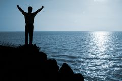 Man in worship position. Against blue sky with sunlight Stock Photos