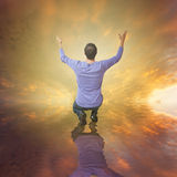 Man worshiping God. Sunset sky and a man standing in his knees worshiping God Royalty Free Stock Images