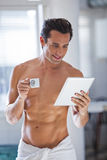 Man Wrapped in Towel holding a cup of coffe and tablet Stock Photography