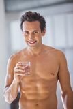 Man Wrapped in Towel holding a glass of water Royalty Free Stock Photo