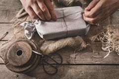 Man is wrapping a gift with natural materials and organic cotton, ecological and biodegradable