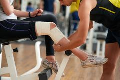Man wrapping girls leg with bandage at gym. Injury from workout. Muscle strain concept stock photography