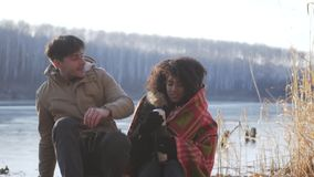 Man wrapping his girlfriend in warm blanket while spending time by frozen lake. Man wrapping his girlfriend in warm blanket by frozen lake during winter vacation stock video