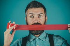 Man wrapping mouth by adhesive tape. Concept freedom of speech and press. International Human Right day. censorship. Brutal bearded male. Mind control and royalty free stock images