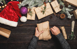 Man wraps Christmas gift on wooden table Stock Image