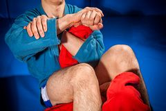 Man wrestler makes submission wrestling. Close-up two wrestlers of grappling and jiu jitsu in a blue and red kimono makes armbar .Submission wrestling on blue stock images