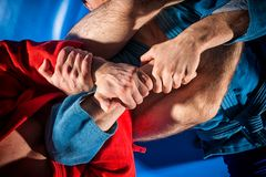 Man wrestler makes submission wrestling. Close-up two wrestlers of sambo and jiu jitsu in a blue and red kimono doing . Man wrestler makes submission wrestling stock photos