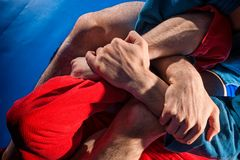 Man wrestler makes submission wrestling. Man wrestlers of grappling and jiu jitsu in a blue and red kimono makes submission wrestling. Fighting techniques stock photos