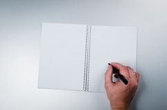 Man write. On a notebook background Royalty Free Stock Photography