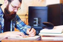 Man write pen table. Man write pen in a note pad on a table Royalty Free Stock Image