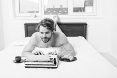 Man writer lay bed bedclothes working book. Writer romantic author used old fashioned typewriter. Author having stock photos