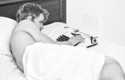Man writer lay bed working on new book. New day brings fresh ideas. Writer author used old fashioned machine instead of. Digital gadget. Morning inspiration stock photos