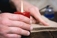 Writer. Man a writer is reading a blank document or letter on his desk in the light of candle royalty free stock images