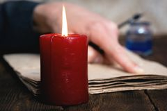 Writer. Man a writer is reading a blank document or letter on his desk in the light of candle royalty free stock photo