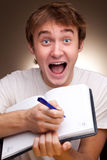 Man writes. A funny young man writes in a notebook Stock Images