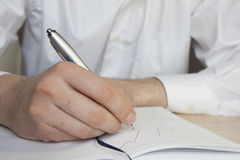 Man writes, business. Man writes in a notebook, hands close up Royalty Free Stock Photo