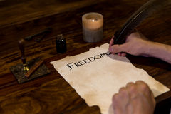 Man writes on document freedom Stock Photo