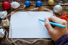 Man writes a list of gifts for the newyear Stock Photos