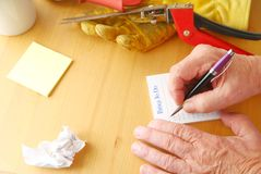 Man writes list next to yard tools. Overhead of man writing a to do list with crumpled paper, notepad, coffee cup, gardening glove and grass cutters Royalty Free Stock Photos