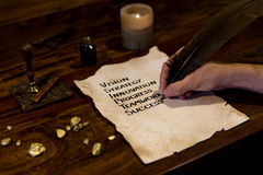 Man writes mystery to success on parchment Stock Photography