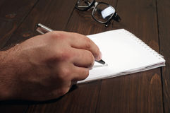 Man writes in a notebook. Closeup of a man writes in a notebook on the office table Royalty Free Stock Images
