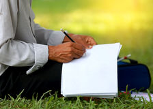 Man writes in a notebook. Man writes in a notebook on his knee while sitting in the park Stock Photos