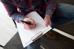 Man writing in his notebook at home. Man writes in a notebook on his knee while sitting on steps. Close up picture taken from high angle of male hand writing on Royalty Free Stock Photography