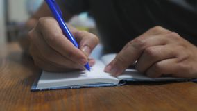 Man writes in notebook. male hand writing in a notepad. concept business education. man makes notes in notebook that stock footage