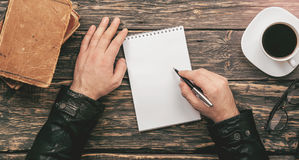 Man writes in notebook sitting at wooden table in cafe. Man writes in a notebook sitting at a wooden table in a cafe, top view Royalty Free Stock Photography