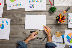 Man writes in notebook on wooden office desktop. Top vew Royalty Free Stock Photography