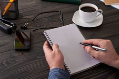 Man writes in a notebook on a wooden table. Accounting. Man working at home. The man writes in a notebook on a wooden table Stock Photo