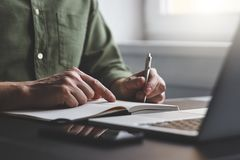 The man writes notes to his diary. In the office stock image