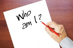 Man writes on a paper sheet Who am I? Royalty Free Stock Photo