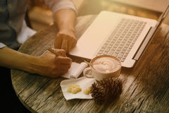 A man writes a pen in a notebook, to work in the office, laptop on  table, a white mug of coffee. Stock Photo