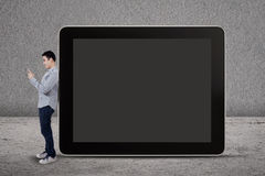A man writes an SMS and standing by a big tablet Stock Photos