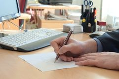 Man writes something on a white paper. Office work Royalty Free Stock Photo