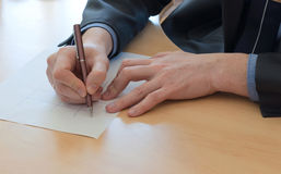 Man writes something on a white paper. Office work Stock Photos