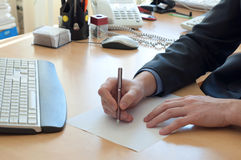 Man writes something on a white paper. Office work Royalty Free Stock Image