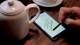 Man writes SOS inscription on the smart phone screen stock footage