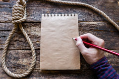 Man writes a suicide note. In the notebook Stock Images