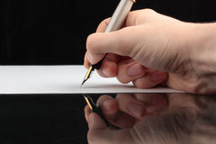 The man writes on a white sheet of a paper Royalty Free Stock Photo