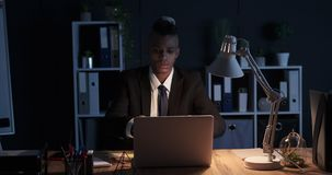 Man writing on adhesive note and sticking it on laptop late at night office. African american businessman writing on adhesive note and sticking it on laptop at stock video