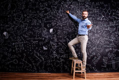Man writing on big blackboard with mathematical symbols Stock Photography