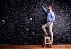 Man writing on big blackboard with mathematical symbols. Hipster teacher writing on big blackboard with mathematical symbols and formulas, standing on step Royalty Free Stock Photo