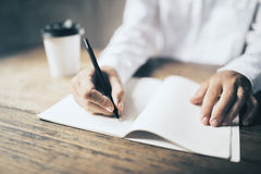 Man writing in blank diary and paper coffee cup on wooden table Stock Photo