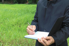 A man writing book on grass background Royalty Free Stock Photos
